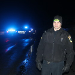 Officer Connor Lapierre of the Fort Kent Police Department mans a roadblock on Aroostook Road as three law enforcement agencies respond to an incident in a residence there on Friday.