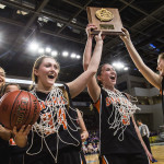 Shead High Schools girls basketball senior captains Katelyn Mitchell (left) and Holly Preston (center) and teammate Cassidy Walker (right) hold their team's championship plaque into the air for cheering fans, surrounded by their other teammates, following their Class D girls final basketball game against Southern Aroostook at the Cross Insurance Center in Bangor on Saturday morning. 