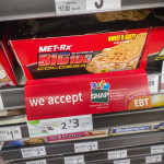 A sign on a sales rack of an energy bar in a 7-Eleven in New York on Sunday, July 27, 2014, promotes the convenience store's acceptance of the SNAP (Supplemental Nutrition Assistance Program).