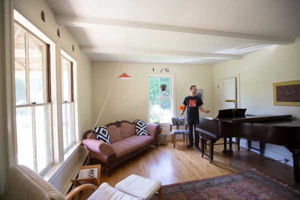 Ryan Blotnick gestures to his fiancee, Keri Kimura (not shown), while placing fresh flowers in the living room of their Southwest Harbor home for incoming Airbnb visitors.
