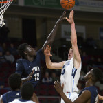 University of Maine's Andrew Fleming (right) puts up a shot past University of New Hampshire's Iba Camara at the Cross Insurance Center in Bangor.