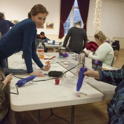 Sara Myrick looks on while a heat gun is applied to a recycled plastic ornament at the EAC's ornament-making party back in November. This weekend Sara will be back with two other instructors for a Card-Making Party.