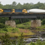 A Central Maine and Quebec Railway locomotive hauls a turbine propeller through Prospect.