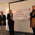 (L-R) Jim Lemieux, Chair of Maine CU League's Social Responsibility Committee, John Murphy, President of the League, are joined by keynote speaker, Jessica Buchanan, a humanitarian aid worker who wrote about being kidnapped and rescued in Somalia, in unveiling the check bearing the record setting amount raised by Maine's credit unions for ending hunger in 2016.