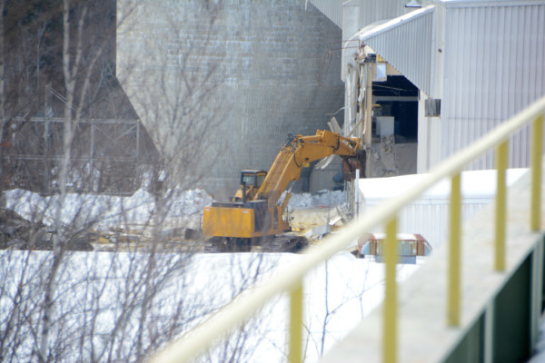 The razing of one of four buildings continued Tuesday at the former paper mill site on Main Street in East Millinocket.
