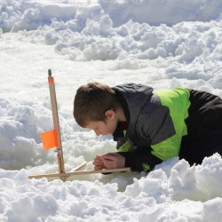 Tyler Knowles, 9, of Brewer tries to get a better look at his bait while ice fishing at Levasseur Pond in Brewer on Sunday, Feb. 19, 2017. Knowles was participating in the Penobscot County Conservation Association's family ice fishing day.