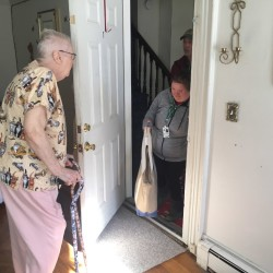 Dottie Ham, 80, opens her door to 32-year-old Caitlyn Gunn, a volunteer who delivers meals in the Bangor area for the Meals on Wheels program.