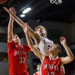 George Stevens Academy's Maxwell Mattson (center) reaches out for a rebound, blocked by Dexter's Brayden Miller (left) and Jacob Bickford during their class C boys semifinal game at the Cross Insurance Center on Friday evening.