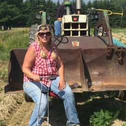 Dixie Shaw, director of hunger and relief services for Catholic Charities Maine, takes a break from planting Farm for ME crops in Caribou last spring.