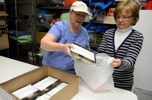 Vicki Haskell (left), Eastern Area Agency on Aging's Hancock County area manager, and Gail Rice, volunteer, organize Meals on Wheels food for distribution.