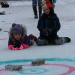 Caroline Pete of Old Town (left) and Grady Ludders of Exeter try their hand at a version of curling on Lac d'Or at Hirundo Wildlife Refuge in Old Town during Winter Fun Day on Feb. 11.