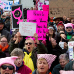 Supporters hold signs during the Women's March on Maine outside the Burton M. Cross building at the Maine State House in Augusta, Jan. 21, 2017. The national rally was in support of women's rights, civil liberties and protection of the planet.