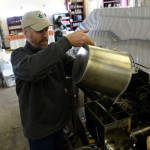 Lee Kinney, owner of Kinney's Sugarhouse in Knox, pours syrup into the evaporator to warm it up and then filter it on Thursday. Kinney produces about 4,000 gallons of syrup from his 10,400 taps.