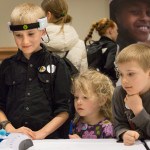 "Charles ""Chachi"" Raychard, 10, of Levant plays an EEG brain game against his brother Max (not shown) while his sister Jane (center), 4, and brother Franklin, 7, watch, at the University of New England's Brain Station at last year's Maine Science Festival."