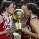 Vinalhaven players (from left) Gilleyanne Davis-Oakes, Paige Dennison and Deja Doughty kiss the gold ball after defeating Shead 55-44 during their Class D girls basketball state championship game at the Cross Insurance Center in Bangor on Saturday. Ashley L. Conti | BDN