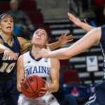 University of New Hampshire's Aliza Simpson (left) reaches to block a shot by University of Maine's Sigi Koizar during a game at the Cross Insurance Center in Bangor in February.