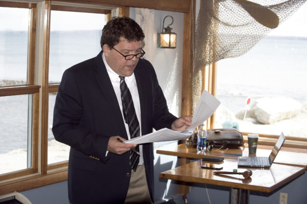 Auctioneer Stefan Keenan of Keenan Auction Company reads through the paperwork before bidding started on the Lobster Pound restaurant in Lincolnville Thursday morning.