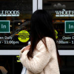 A customer exits a Whole Foods Market in New York City. A brand of cheese sold by the company at its Portland location are being recalled.