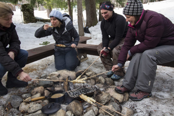 Participants in the 2017 Maine Becoming an Outdoors-Woman (BOW) Winter Skills Weekend cook pretzels over a campfire while learning about outdoor cooking on Feb. 26, at the University of Maine Bryant Pond 4-H Camp and Learning Center.