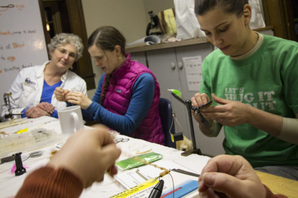 Maine Guide Nancy Taylor (from left) teaches Anya Roberts of Boston, Mass. and Ashley Rice of Farmingdale how to tie fishing flies during her free time after dinner on Feb. 25, during the Becoming an Outdoors-Woman (BOW) Winter Skills Weekend at the University of Maine Bryant Pond 4-H Camp and Learning Center.