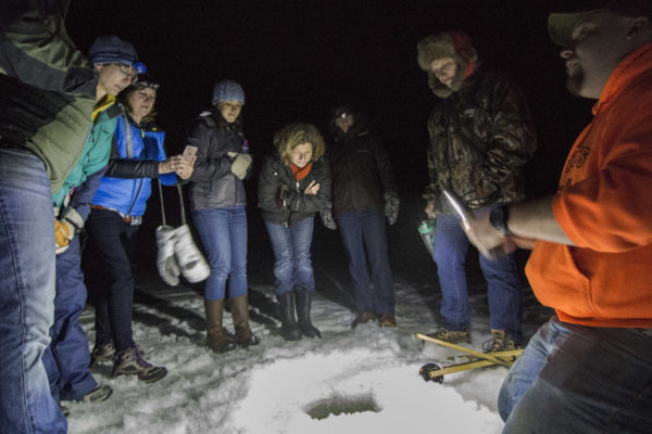 Participants of the 2017 Becoming an Outdoors-Woman (BOW) in Maine Winter Skills Weekend gather around an ice fishing hole on Bryant Pond to learn about cusk fishing on Feb. 24, at the University of Maine Bryant Pond 4-H Camp and Learning Center.