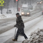 A man looks up Congress Street in Portland while crossing in the snow on Feb. 9.