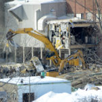 An excavator razes one of four buildings to be demolished at the former paper mill site on Main Street. A fire broke out at the site Monday evening.