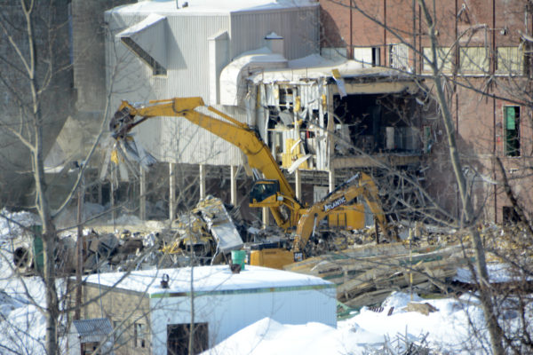 An excavator tears down one of four buildings to be demolished at the former paper mill site on Main Street, Feb. 7, 2017.