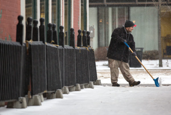 Darrick Deshane shovels the sidewalk outside Paddy Murphy's on Tuesday morning as part of a group of three men from Hopkins Landscaping, including Nick Watson and Michael Deshane (not shown), who were clearing downtown sidewalks as good samaritans. &quotWe don't want anybody getting hurt because it's nasty out,&quot said Watson.
