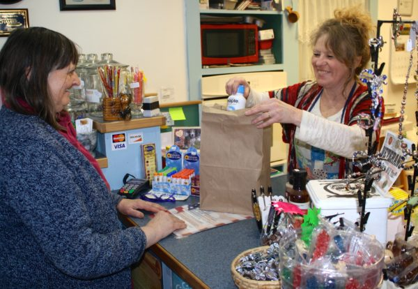Cheryle Matowitz, right, owner of Bread of Life Bulk Food in Presque Isle, bags up some pure maple water for customer Diane Andrews of Hamlin. The raw sap contains numerous nutrients and vitamins and is becoming a popular beverage.