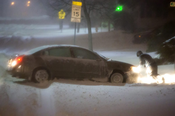 A person pushes their car out of a snow covered road in Bangor late Tuesday.