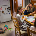 Megan Stover sits at the kitchen table after dinner with her three daughters (from left) Andie, 5, Madison, 10, and Nellie, 7, at their home in Scarborough.