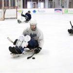 "BANGOR, Maine -- 03/16/2017 -- Dave Taplin (center) moves the puck around during sled hockey practice at Sawyer Arena in Bangor Thursday. The group has been playing for 14 years and consists of disabled and able-bodied athletes. ""We're just looking for anybody to play right now. We have plenty of gear, sleds, helmets, and sticks we just need people to play,"" said Keith Skeffington. Sled hockey is just like stand-up hockey, except athletes sit in a sled that is three inches off the ice. ""It's for people with lower limb disabilities. You have to have use of your upper body,"" Skeffington explained. Interested athletes can contact the team at bangorsledhockey@gmail.com. Ashley L. Conti 
