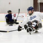 Scott Mahon (right) clears the puck during sled hockey practice at Sawyer Arena in Bangor on Thursday. The group consists of disabled and able-bodied athletes.