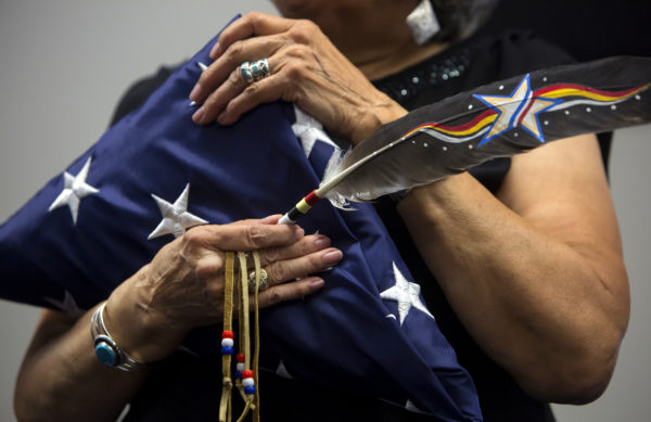 Sylvia Polchies holds an American eagle feather and a folded American flag that she received on behalf of her late father, Henry Sockbeson, during a ceremony to honor six members of the Passamaquoddy Tribe who fought in World War I on Sunday in Indian Township, July 17, 2016.