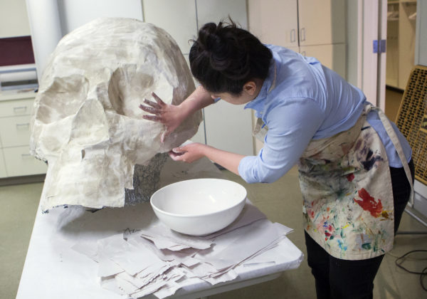 Kat Johnson, education coordinator, adds pieces to a giant paper mache human skull at the University of Maine Museum of Art in Bangor Saturday. The sculpture will be on display at the library later in March and will be unveiled at a reception on March 28.