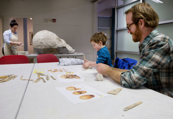 Brian Hinrichs (right) and Nathan Hinrichs, 4, make clay skull sculptures while Kat Johnson adds pieces to a giant paper mache human skull at the University of Maine Museum of Art in Bangor Saturday. The sculpture will be on display at the library later in March and will be unveiled at a reception on March 28.