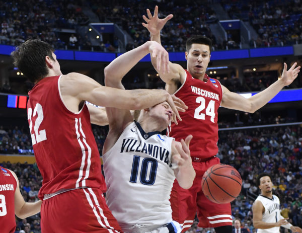 Wisconsin's Ethan Happ (left) blocks a shot by Villanova's Donte DiVincenzo (10) as Wisconsin's Bronson Koenig (24) backs up the play during Saturday's NCAA tournament second-round game at KeyBank Center. Wisconsin won 65-62.