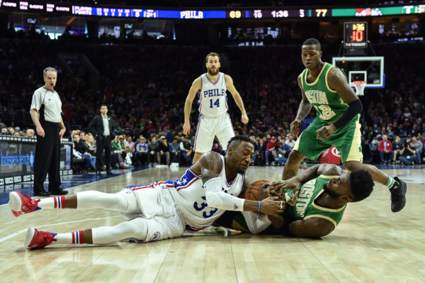 Philadelphi's Robert Covington (33) and Boston's Jaylen Brown (7) battle for a loose ball during the third quarter of Sunday's NBA game at the Wells Fargo Center in Philadelphia. The 76ers won 105-99.