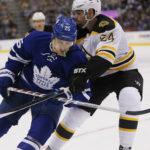 Boston defenseman Adam McQuaid (right) knocks the puck away from Toronto's James van Riemsdyk during the second period of Monday night's game at the Air Canada Centre in Toronto. The Maple Leafs won 4-2.
