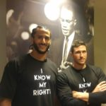 "NFL quarterback Colin Kaepernick, left, stands with Christopher Petrella of the Bates College Office of Equity and Diversity during a January session of Kaepernick's ""Know Your Rights"" Camp at the Audubon Ballroom in New York City."