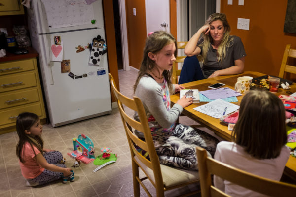 Megan Stover sits at the kitchen table after dinner with her three daughters (from left) Andie, 5, Maddie, 10, and Nellie, 7, at their home in Scarborough.