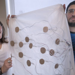 University of Maine neuropsychology student Katrina Daigle and electrical engineering student Ahmed Almaghasilah hold a device that records data while a person is sleeping. The mattress cover is outfitted with sensors to record movement while a person is asleep. The patented technology, developed at UMaine, is being used to study sleep disorders.