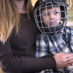 DEDHAM, MAINE -- 03/13/2017 -- Wyatt Beauchamp, 6, is held by his mother Kristin Beauchamp after he had a small seizure.  Wyatt has epilepsy, causing seizures ranging from a few seconds of inactivity to major episodes when he falls to the floor and his body starts to shake. He has to wear a helmet to provide some protection during the numerous falls throughout the day.