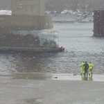 As several first responders watch from shore in Brewer, a diver reaches a young man partially submerged in the icy Penobscot River under the I-395 bridge Wednesday afternoon.