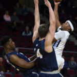 The University of Maine's Wes Myers (right) puts up a shot over the University of New Hampshire's David Watkins (left) and Luke Rosinski during a game at the Cross Insurance Center in Bangor on Jan. 19. Myers has been reinstated to the team after being suspended in February following an altercation with a teammate.