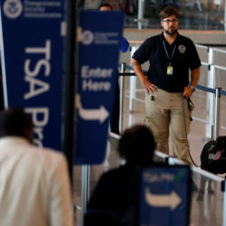 A TSA security officer and his dog scan departing passengers at Lindbergh Field airport in San Diego, California, July 1, 2016.