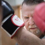BRUNSWICK, MAINE -- 03/16/17 -- John Moulton, 65, of Harpswell punches trainer Zach Hartman's glove during a Rock Steady Boxing class in Brunswick. Rock Steady Boxing is an exercise program adapted to people with Parkinson