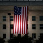 The Pentagon unveils a large American flag at sunrise on Thursday, Sept. 11, 2014, near the site where the building was struck on 9/11.