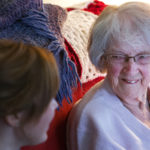 ORONO, Maine -- 03/21/2017 -- Joan Logue smiles as she listens to Emma Brickman's story at Logue's home in Orono Tuesday. Brickman visits with Logue one hour a week as part of Project Generations, a new program supported by the Eastern Area Agency on Aging and the Maine Center on Aging aimed at connecting student volunteers with senior citizens in the area, helping students appreciate the challenges of aging in place and giving seniors a lively young connection to the community. Ashley L. Conti | BDN